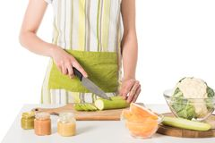 cropped shot of woman cutting zucchini by knife at table with puree jars, cauliflower and pumpkin royalty free stock photo
