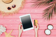 Cropped shot of woman holding digital tablet with credit card on pink. Wooden surface stock image