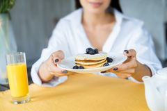 cropped shot of woman with pancakes served with blueberries on plate in hands stock photography