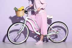 cropped shot of woman in pink clothing on bicycle with pineapple and bananas stock image