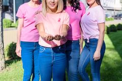 Women in pink t-shirts with ribbons. Cropped shot of woman in pink t-shirts with ribbons standing together Stock Image