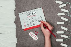 Cropped shot of woman pointing at date in calendar with pills, menstrual pads and tampons around. On grey surface royalty free stock photo
