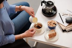 Cropped shot of woman pouring cream into cup of coffee with cane sugar and piece of cake. On coffee table stock photo