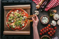 cropped shot of woman pouring oil onto delicious pizza royalty free stock photo