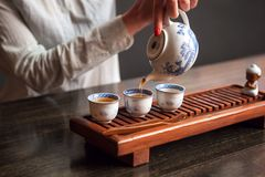 Woman pouring tea in traditional chinese teaware. Cropped shot of woman pouring tea in traditional chinese teaware royalty free stock images