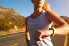 Cropped shot of woman running and checking her sports watch Stock Photos