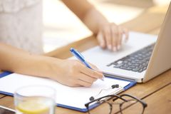 Close-up of woman hand making notes and using laptop royalty free stock photo