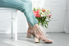 cropped shot of woman sitting on chair with flowers on floor in front of white royalty free stock image