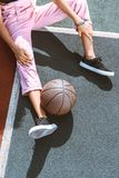 Cropped shot of woman sitting on ground of sports field with basketball ball. Near her leg royalty free stock images