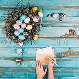 cropped shot of woman writing easter greeting on blue royalty free stock photography