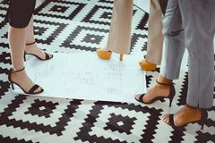 Cropped shot of women on high heels shoes standing. On blueprint stock photography