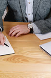 Cropped shot of workspace with man's hands with watch and work s Royalty Free Stock Image