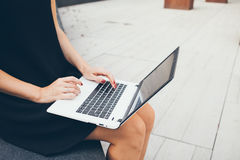 Cropped shot of young female using laptop while sitting in a backyard of office building. Looking up for information on the internet, reading news, surfing Stock Photography