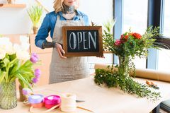 Cropped shot of young florist holding open sign. In flower shop stock images