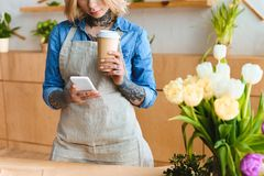 Cropped shot of young florist holding paper cup and using smartphone. In flower shop royalty free stock photography