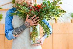 Cropped shot of young florist holding vase with beautiful bouquet. In flower shop stock photo