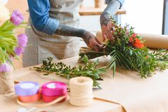 Cropped shot of young florist with tattooed hands arranging flower bouquet. At workplace stock image