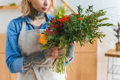 Cropped shot of young florist with tattoos holding flower. Bouquet stock photography