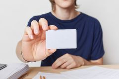Cropped shot of young male hands holds blank card with copy space for your text or advertising content. Young businessman wears t. Shirt shows business card Stock Photos
