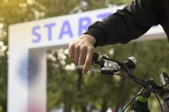 Cropped shot of young man on the bicycle on the start point of the cycling race. Start text. Bokeh background royalty free stock photos