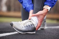 Cropped shot of a young man holding his ankle in pain sprain a f. Cropped shot of a young man holding his ankle in pain while running stock photography