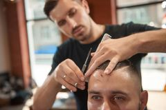 Young man at the barbershop. Cropped shot of a young men getting a haircut at the barbershop stock photography