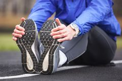 Cropped shot of a young runner stretching after workout. Stock Photo