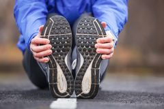 Cropped shot of a young runner stretching after workout. Stock Photography