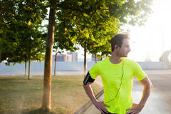 Cropped shot of young sports man resting after jogging in the park while listening to music in headphones Stock Photos