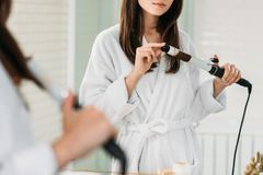 Cropped shot of young woman. In bathrobe using hair curler at mirror in bathroom royalty free stock photography