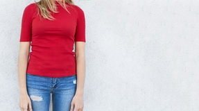 Cropped shot of young woman posing against white studio wall, dressed in fashionable jeans and red sweater with blank space for yo Stock Photo