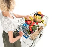 cropped shot of young woman pushing shopping trolley with grocery bags and plastic bottle of water stock images