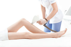 Cropped shot of young woman receiving laser skin care on leg Royalty Free Stock Photos
