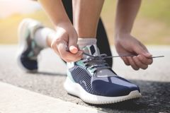 Cropped shot of young women runner tightening running shoe laces.  Royalty Free Stock Photography