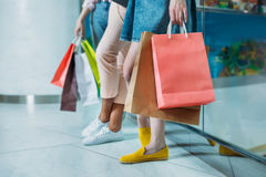 Cropped shot of young women with shopping bags standing in shopping mall Stock Photos