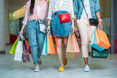 Cropped shot of young women with shopping bags walking in shopping mall Stock Image