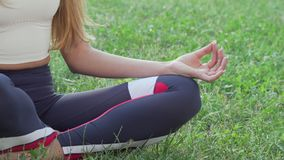 Cropped sliding shot of a female meditating in lotus asana