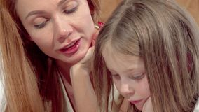 Cropped sliding shot of a mother and daughter reading a book together stock footage