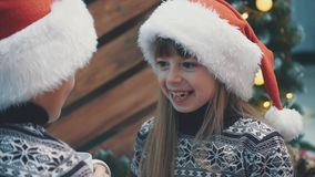 Cropped slowmotion of funny baby in santa hat, with evil genius laugh, looking at her brother with facial expression as