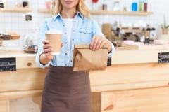 cropped strzał kelnerki mienia kawa iść w papierowej filiżance i brać oddalonego jedzenie Obrazy Stock