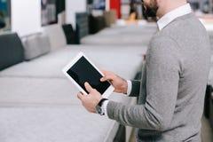 cropped strzał mężczyzna używa cyfrową pastylkę z pustym ekranem w meblarskim sklepie obrazy stock