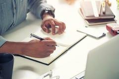 Cropped strzał mężczyzna writing na notatnika papierze na miejscu pracy zdjęcie stock
