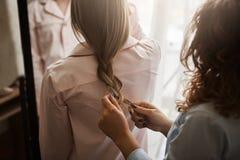 Cropped strzał matki i córki pozycja w nightwear podczas gdy mama robi warkoczowi dla cutie, zgrzywionego włosy i patrzeć jej, Obraz Stock