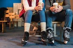 cropped strzał potomstwa dobiera się w łyżwach trzyma kawowymi iść Zdjęcie Stock