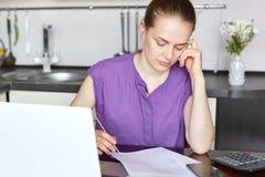 Cropped strzał przyjemna przyglądająca kobieta bez uzupełniał, ubiera niezobowiązująco, koncentrujący w dokumentach, kalkuluje ro Obraz Stock