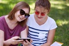 Cropped strzał rozochoceni żeńscy młodzienowie zadawalał wyrażenia, zegarek komediowy przez telefonu komórkowego online, być w wy fotografia stock