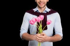 Cropped strzał uśmiechnięci młodego człowieka mienia menchii tulipany na czerni Obrazy Royalty Free