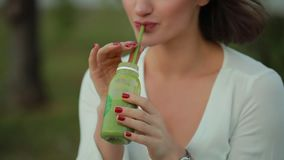 Cropped unrecognizable woman drinking green smoothie outdoor. Healthy food stock video