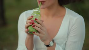 Cropped unrecognizable woman drinking green smoothie outdoor. Healthy food stock video footage