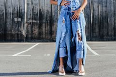 Cropped view of afro girl in jeans clothes posing for fashion shoot. On street stock photography